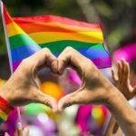 hand-making-love-sympbol-and-pride-flag